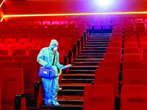सिनेमा घर को सेनेटाइज करता कर्मी। - Dainik Bhaskar