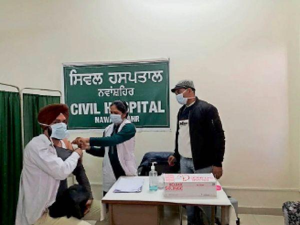 कोरोना वैक्सीन लगवाते अधिकारी। - Dainik Bhaskar