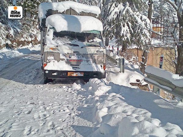 बर्फबारी के कारण एक ट्रक चालक को अपना ट्रक सड़क के किनारे खड़ा करना पड़ा।