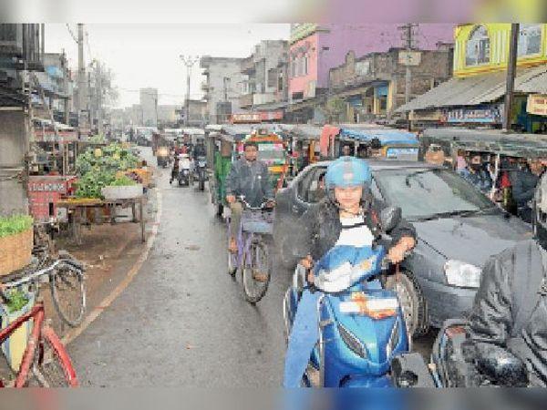 बारिश से भींगी सड़क से आवाजाही करती युवती व अन्य लोग। - Dainik Bhaskar