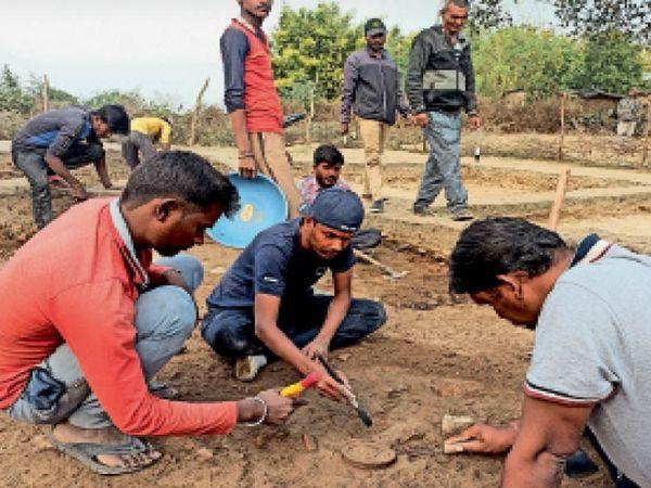 ऐरण में खुदाई के दौरान मिल रहे अवशेषों को देखती टीम। - Dainik Bhaskar
