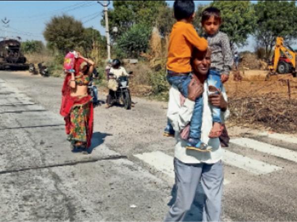 श्रीमाधोपुर. किसानों के चक्काजाम के कारण बस से उतरकर दो बच्चों को कंधे पर बैठाकर पैदल ही परिवार के साथ रवाना होता कालूराम। - Dainik Bhaskar