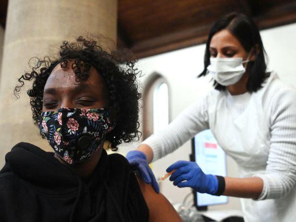सोमवार को लंदन के एक अस्पताल में वैक्सीनेशन कराती महिला। ब्रिटेन सरकार ने कहा है कि वो अपनी वयस्क आबादी को वैक्सीनेट करने के बाद बचे ओवर स्टॉक को दूसरे देशों को देने पर विचार कर रही है।