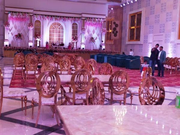 स्टेज में मेहमानों के लिए लगी कुर्सियां।