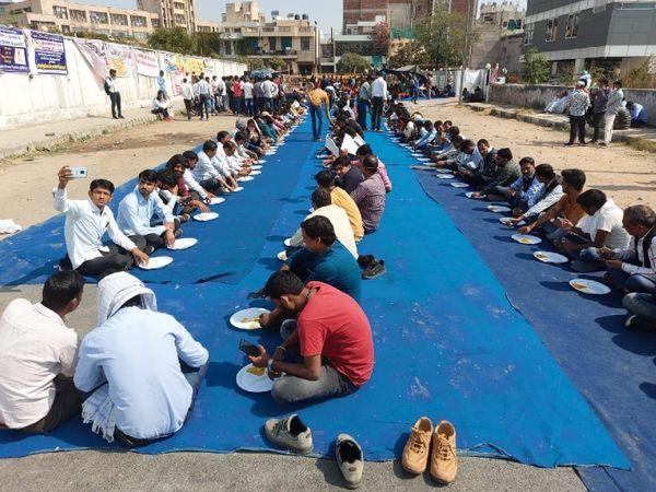 धरने पर बैठे अभ्यर्थियों को पंगत में बैठाकर खाना खिलाते हुए।