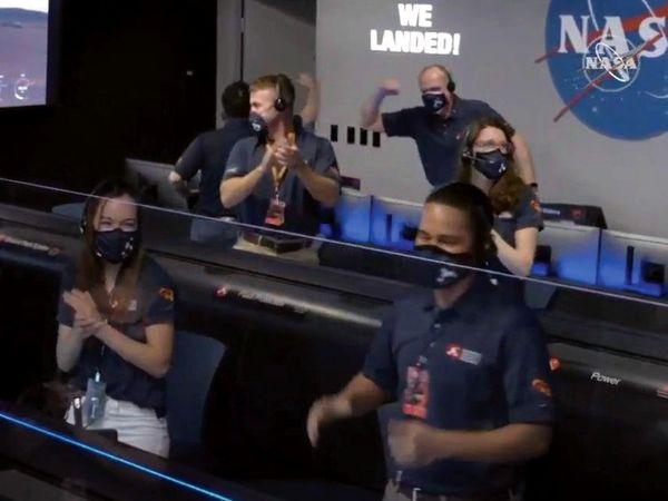सफल लैंडिंग की खुशी मनाते यूएस एयरोनोटिक्स और स्पेस ऐडमिनिस्ट्रेशन के कर्मचारी।