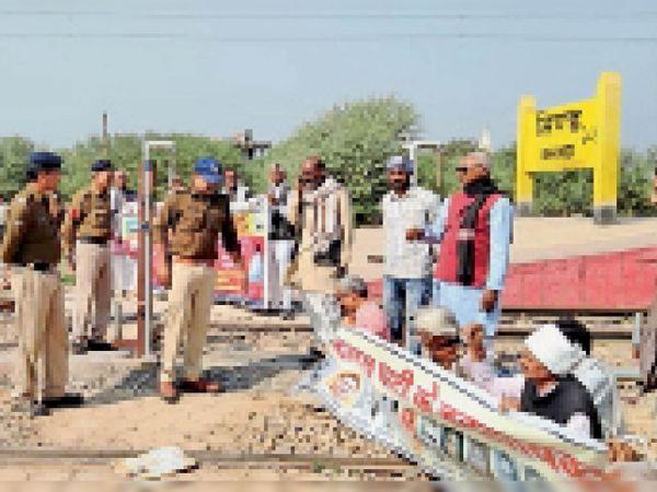 पुलिस विरोध प्रदर्शन के दौरान किसानों को पटरी से उठने के लिए कहती हुई। - Dainik Bhaskar