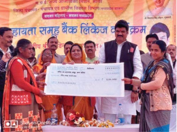 समूह की महिलाओं को चैक बांटते हुए मंत्री राजपूत। - Dainik Bhaskar