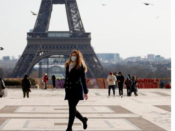 11 फरवरी को पेरिस में एफिल टॉवर के सामने से गुजरती महिला। फ्रांस में इस हफ्ते संक्रमितों की संख्या तेजी से बढ़ी है। सरकार ने मास्क मेंडेटरी कर दिया है, लेकिन लॉकडाउन जैसे सख्त कदम उठाने से इनकार कर दिया है। - Dainik Bhaskar