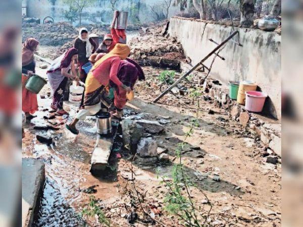 ट्यूबवेल से बर्तनों में पानी भरतीं महिलाएं। - Dainik Bhaskar