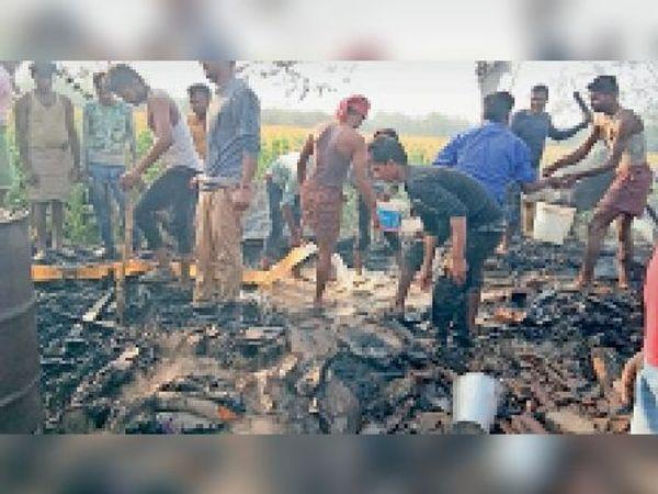 आग बुझाते ग्रामीण। - Dainik Bhaskar