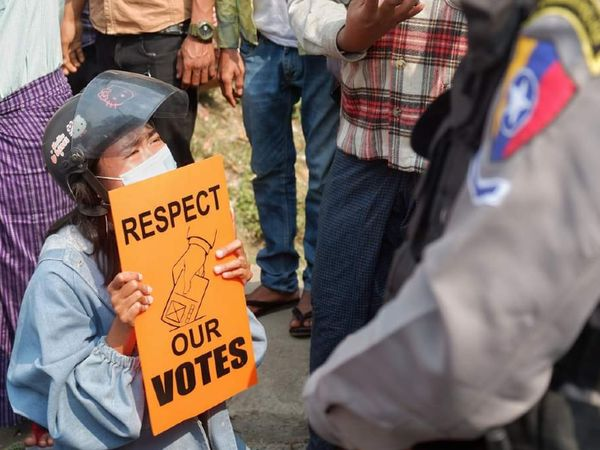 म्यांमार के मांडले में सोमवार को एक सैनिक को बैनर दिखाती बुजुर्ग महिला। इस पर लिखा था- हमारे वोट का सम्मान करें। म्यांमार में 1 फरवरी को सेना ने चुनी हुई सरकार का तख्ता पलट दिया था। - Dainik Bhaskar