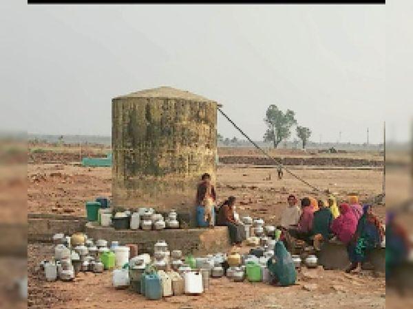 मंगलवार को डाबली गांव से बाहर स्थित बोर से पानी भरने के लिए पहुंचे ग्रामीण, अपनी बारी का इंतजार करते हुए। - Dainik Bhaskar