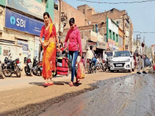 शहर के बताशा बाजार के सामने पाइप लाइन टूटने के कारण सड़क पर पसरी कीचड़ से निकलते लोग। - Dainik Bhaskar