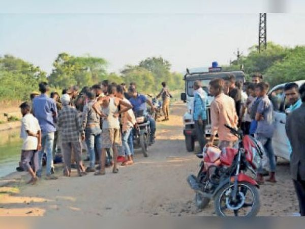 शहर के बाईं मुख्य नहर में मिली लाश को देखने एकत्रित ग्रामीण लोग। - Dainik Bhaskar