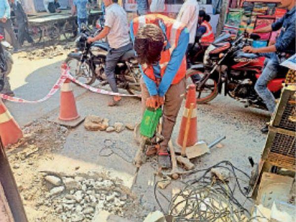 जौरा कस्बे के मुख्य बाजार मे गैस पाइप लाइन बिछाता युवक। - Dainik Bhaskar