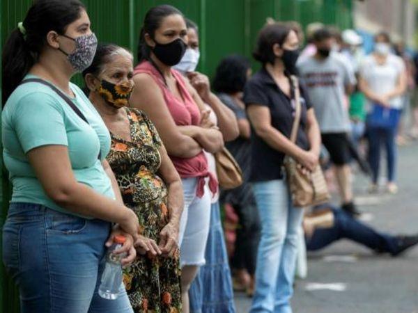 ब्राजील के साओ पाउलो में वैक्सीनेशन सेंटर के बाहर मौजूद महिलाएं। यहां वैक्सीनेशन की रफ्तार बेहद धीमी है और देश में संक्रमण से मरने वालों का आंकड़ा तेजी से बढ़ रहा है। (फाइल)