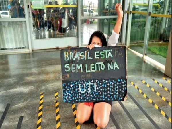 ब्राजील की राजधानी ब्राजीलिया में सभी आईसीयू बेड भर गए हैं। स्वास्थ्य मंत्रालय में लड़की आईसीयू में बेड नहीं होने की बात लिखकर प्रदर्शन करने पहुंची। - Dainik Bhaskar