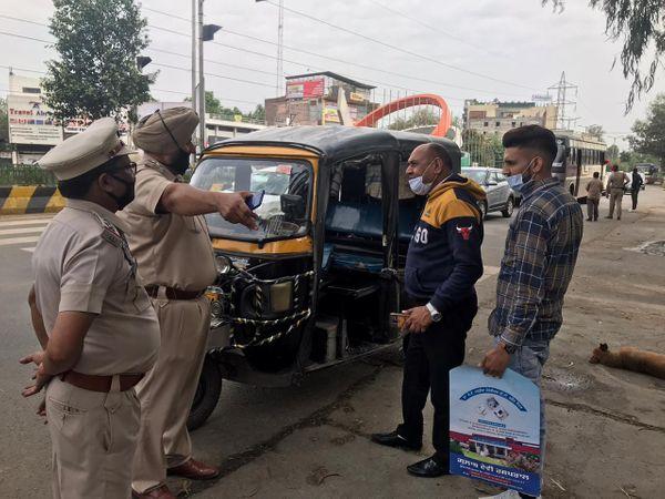 सही ढंग से मास्क न पहनने वाले ऑटो चालक को कोविड टेस्ट के लिए कहते पुलिसकर्मी।