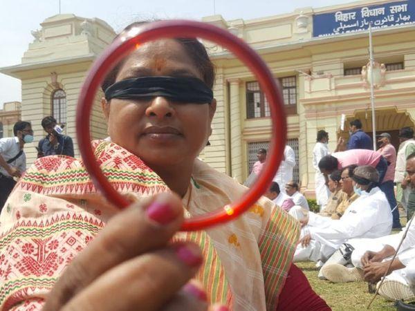 विपक्षी दल की एक महिला विधायक सत्तारूढ़ नेताओं को चूड़ी दिखाते हुए।