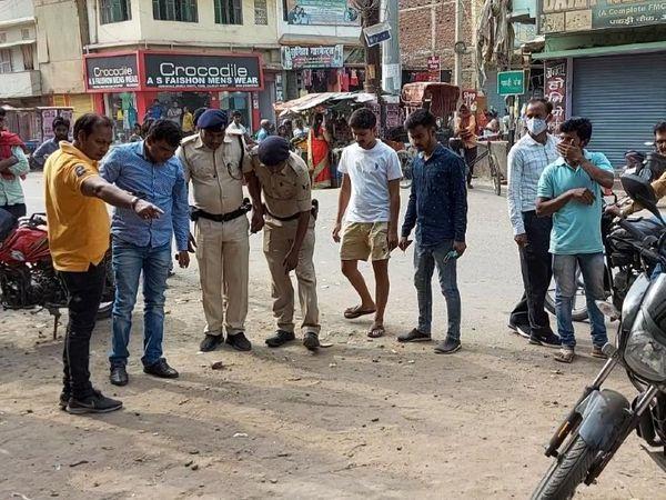 घटनास्थल से खोखा बरामदगी के दौरान पुलिसकर्मी। - Dainik Bhaskar
