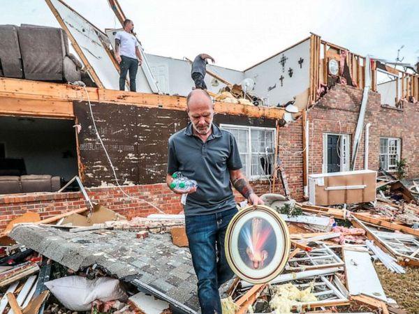 न्यूनान के कोवेता काउंटी में तूफान गुजरने के बाद जरूरी सामान इकट्ठा करता एक व्यक्ति।