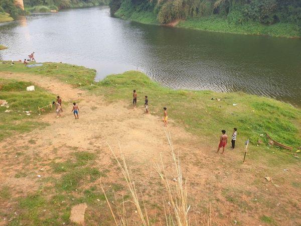 मलप्पुरम और कोझीकोड जिले से होकर गुजरने वाली चलियार नदी के किनारे बच्चे फुटबॉल खेल रहे हैं।