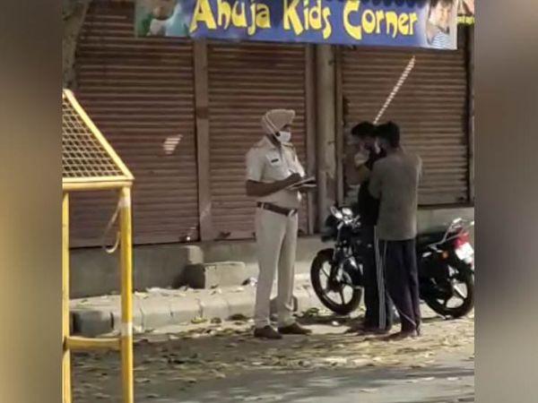 फतेहाबाद शहर में एक नाके पर बाइक सवार युवकों को रोककर पूछताछ करते पुलिसकर्मी।