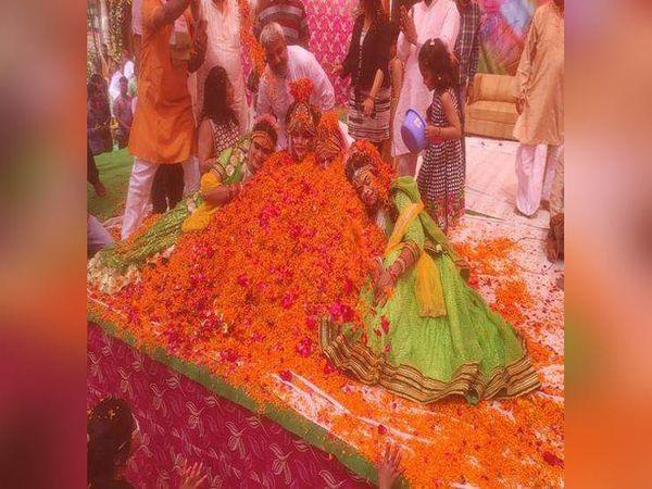 लुधियाना के हंबड़ा रोड स्थित गोविंद गोधाम में फूलों की होली के दौरान फूलों के ढेर में दबे राधा-कृष्ण की झांकी में नृत्य करने वाले कलाकार। - Dainik Bhaskar