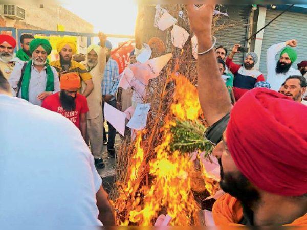 कुंडली बॉर्डर पर कृषि कानूनों की प्रतियां जलाते किसान। - Dainik Bhaskar