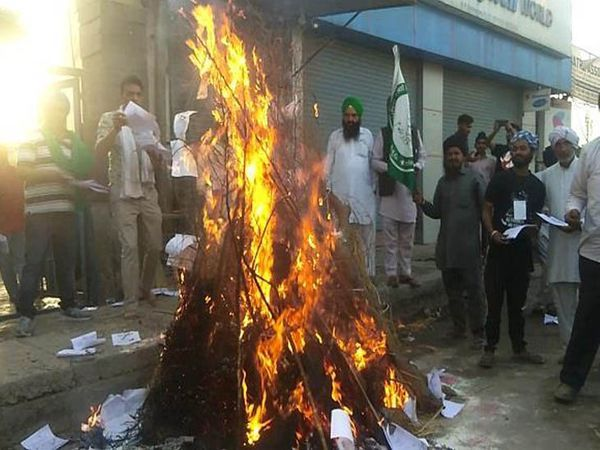 सोनीपत के कुंडली में हरियाणा-दिल्ली बॉर्डर पर होलिका दहन में कृषि कानूनों की प्रतियां जलाकर विरोध जताते किसान संगठनों के लोग।