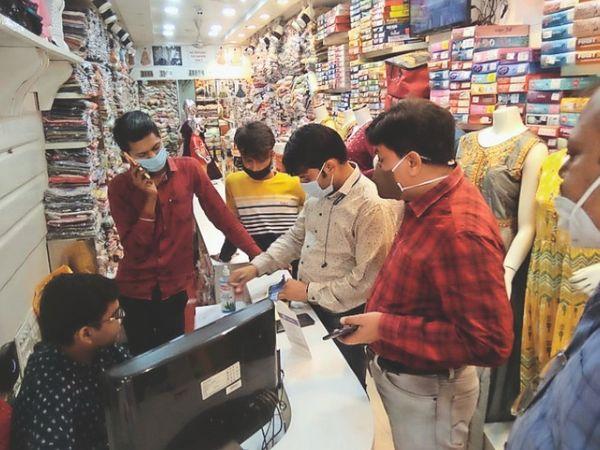 सदर बाजार मुरार में कपड़े की दुकान का चालान बनाते अफसर। - Dainik Bhaskar