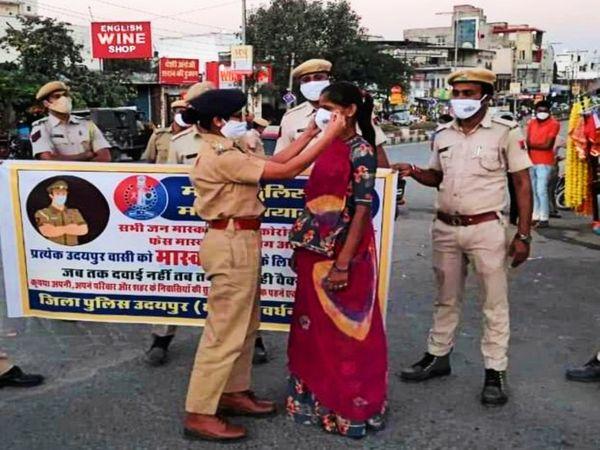 लापरवाह लोगों को मास्क लगा समझाइश करती उदयपुर पुलिस की महिला अधिकारी। - Dainik Bhaskar