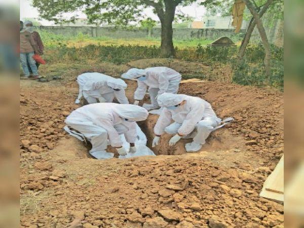 मृतक के शव को कब्रिस्तान में दफनाते नपा के कर्मचारी। - Dainik Bhaskar