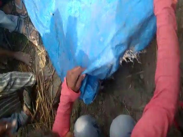 मारे गए बच्चों के शवों को तिरपाल से ढंकते हुए परिजन और गांव के लोग।