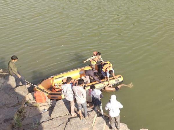 पानी से बाहर निकालते हुए किशोर का शव। - Dainik Bhaskar