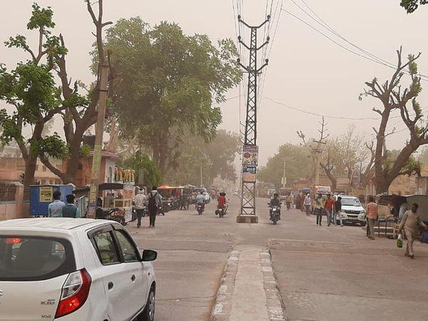 तारानगर। कस्बे की मुख्य सड़क पर धूलभरी आंधी से गुजरते वाहन व लोग। - Dainik Bhaskar