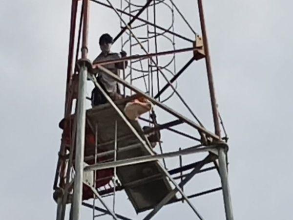 पेट्रोल की बोतलें लेकर टॉवर पर चढ़े बुजुर्ग। - Dainik Bhaskar