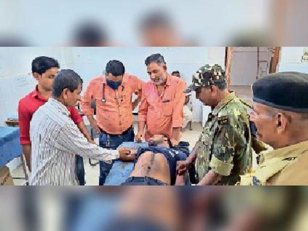 सदर अस्पताल में इलाजरत घायल युवक और मौके पर मौजूद पुलिस। - Dainik Bhaskar