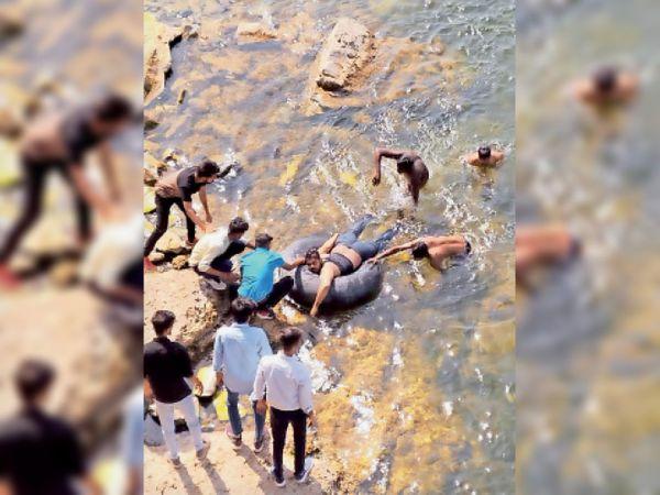 पालोदा. घटनास्थल पर पानी से शव को बाहर निकालते हुए दोस्त। - Dainik Bhaskar