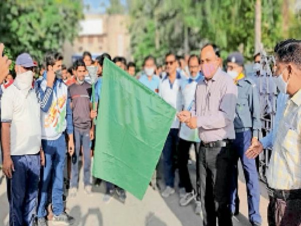 राजस्थान दिवस पर मैराथन से पहले हरी झंडी दिखाते एडीएम। - Dainik Bhaskar
