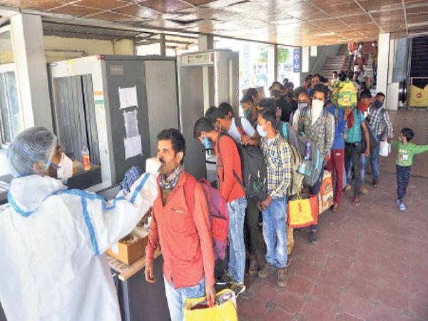 मंगलवार को रेलवे स्टेशन पर यात्रियों की जांच करते स्वास्थ्य विभाग के कर्मचारी। - Dainik Bhaskar