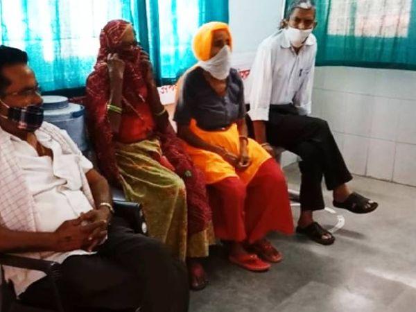 अलवर में टीकाकरण के लिए अपनी बारी का इंतजार करती महिलाएं।