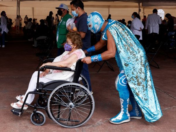 मैक्सिको की राजधानी मैक्सिको सिटी में एक बुजुर्ग महिला को वैक्सीन लगाने के प्रेरित करता रेसलर (WWE फाइटर)।