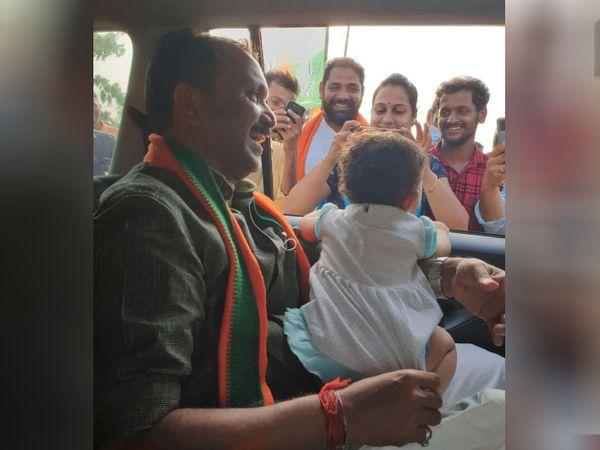 चुनावी सभा के बाद गाड़ी के अंदर से एक बच्ची को दुलारते हुए के. सुरेंद्रन। सुरेंद्रन पिछली बार बहुत ही कम वोटों से चुनाव हार गए थे।