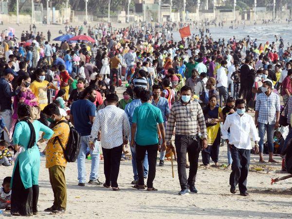 कोरोना के बढ़ते खतरे के बीच मुंबई के जुहू बीच पर लोग बेफिक्र होकर घूमते दिखे।