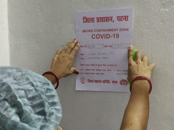 पटना के एक माइक्रो कंटेनमेंट जोन में पोस्टर चिपकाता स्वास्थ्यकर्मी। - Dainik Bhaskar
