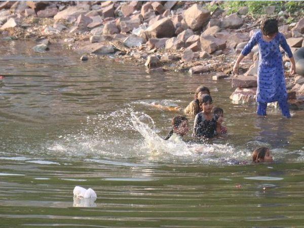 बड़े तालाब में गर्मी से निजात पाने के लिए बच्चे पानी में नहाते हुए। - Dainik Bhaskar