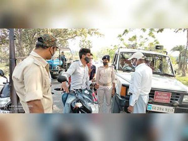 हेलमेट और मास्क की जांच करते पुलिस अधिकारी और जवान। - Dainik Bhaskar