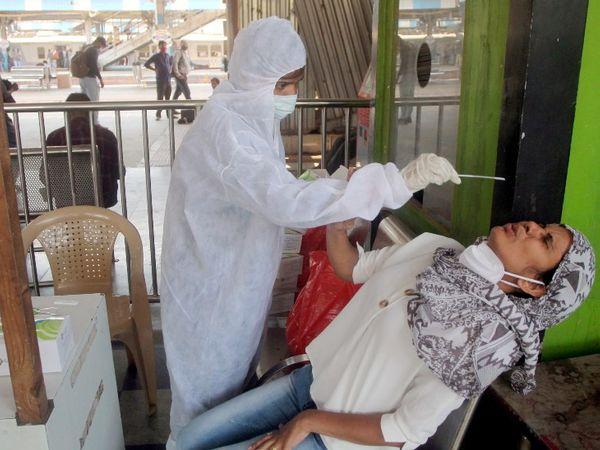 मुंबई के दादर में एक मरीज का कोरोना का नमूना लेता BMC का एक स्वास्थ्यकर्मी।